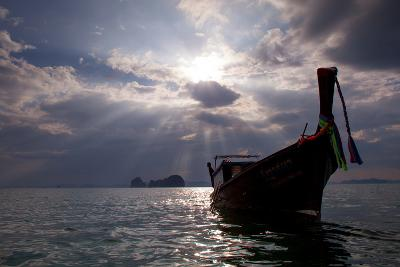 Andaman Sea: A Man Leans Off of a Long Tail Boat in the Andaman Sea under Rays of Light-Ben Horton-Photographic Print