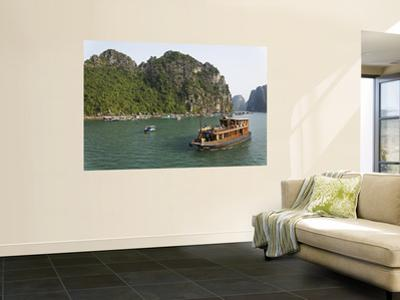 Tourist Cruise Boat Passing Typical Floating Village Among Limestone Islands of Halong Bay