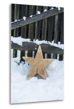 Raw Wooden Star in Front of Fence in the Snow