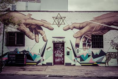 Graffiti of Michelangelo´s God and Adam´s hands in Williamsburg, Brooklyn, New York, USA