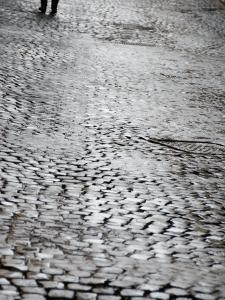 Person's Feet Walking Down Cobblestone Street in Rome, Italy by Andrea Sperling