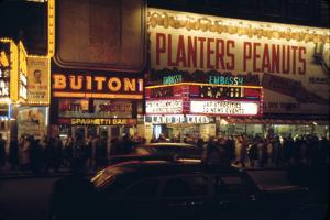 1945: Embassy Theater Showing Newsreel Format Films at Night, Times Square, New York, NY by Andreas Feininger