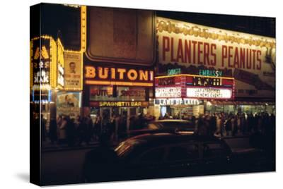 1945: Embassy Theater Showing Newsreel Format Films at Night, Times Square, New York, NY