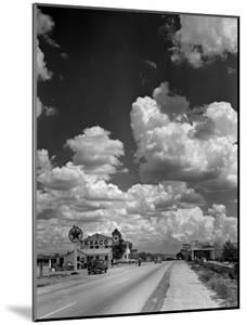 Cumulus Clouds Billowing over Texaco Gas Station along a Stretch of Highway US 66 by Andreas Feininger