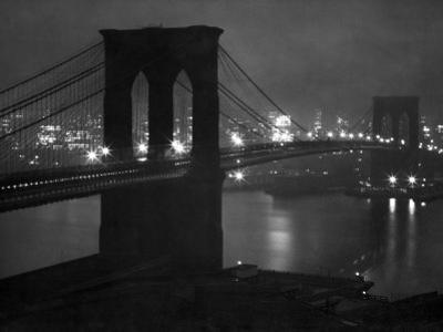 Glittering Night View of the Brooklyn Bridge Spanning the Glassy Waters of the East River