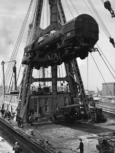 Locomotive Hoisted by Merritt-Chapman-Scott Crane Headed for France to Boost the Postwar Effort by Andreas Feininger