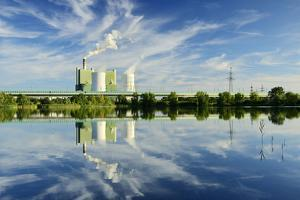Germany, Saxony-Anhalt, Schkopau, brown coal power station is reflected in pond by Andreas Vitting