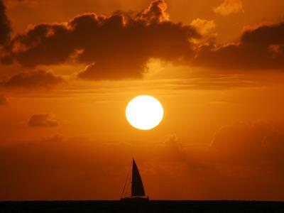 Sailboat on Ocean in Front of Setting Sun