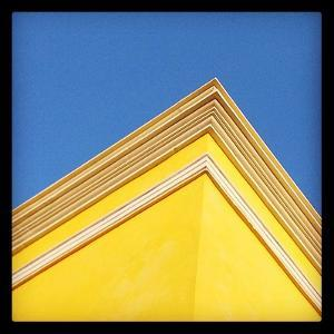 The Corner of a Yellow Building Against a Clear Blue Sky by Andrew Evans