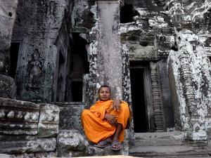 A Buddhist Monk Relaxes in the Bayon Temple, Angkor, Unesco World Heritage Site, Cambodia by Andrew Mcconnell