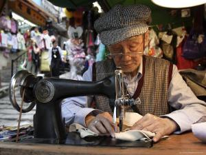 A Tailor at Work in Hong Kong, China by Andrew Mcconnell