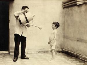 Man Is Sprinkling Boy with Water from Watering Can, 20th Century by Andrew Pitcairn-knowles