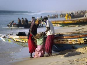 Mauritania, Nouakchott Fishermen Unload Gear from Boats Returning to Shore at Plage Des Pecheurs by Andrew Watson