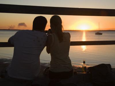 Queensland, Fraser Island, A Couple with Video Camera in Hand Watch Sunset from a Pier, Australia