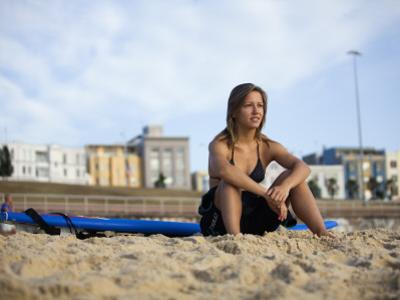 Woman Sitting on Beach with Surfboard at Bondi Beach