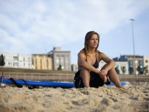 Woman Sitting on Beach with Surfboard at Bondi Beach by Andrew Watson