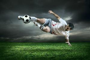 Football Player with Ball in Action Outdoors by Andrey Yurlov