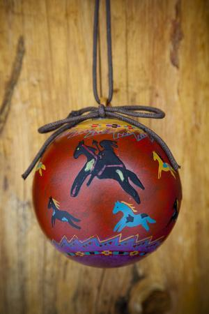 Christmas ornament of a painted ball with colorful Native American horses