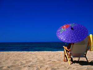 A Girl on the Beach Shading Under a Colourful Umbrella, Waikiki, Oahu, Hawaii, USA by Ann Cecil