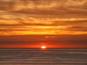 USA, California, La Jolla, Fiery sun drops into the Pacific Ocean by Ann Collins