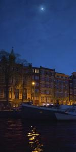 View of Amsterdam Canal at Night by Anna Miller