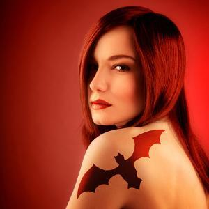 Photo of Beautiful Sexy Girl with Bat Tattoo on Shoulder Isolated on Red Background, Halloween Holi by Anna Omelchenko