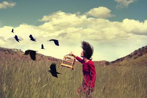 A Girl Walking through a Field with a Flock of Ravens or Crows Toned with a Retro Vintage Instagram by Annette Shaff