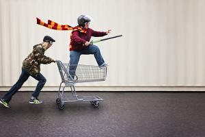 Two People Dressed up as Super Heroes or Characters Horsing around in a Shopping Cart with Goggles by Annette Shaff
