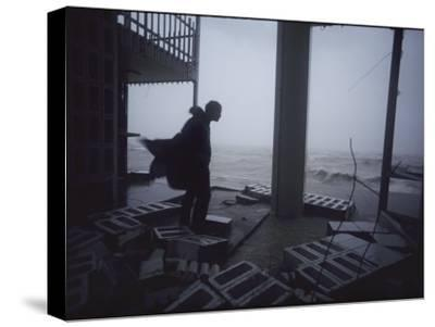A Silhouetted Figure Observes Hurricane Wreckage