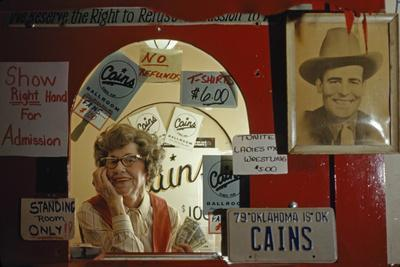 An elderly woman stands in the ticket window of famed Cain's Ballroom.