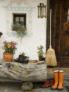 Boots, a Broom and Flowers Outside a Chalet by Annie Griffiths Belt