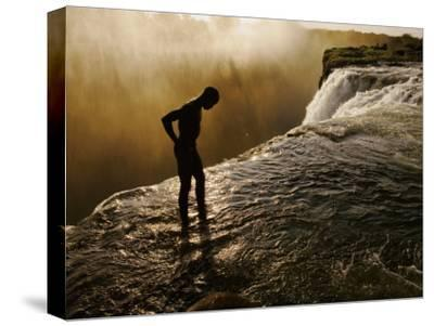 Swimmer Stands at the Lip of a Hidden Pool at Victoria Falls