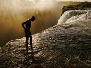 Swimmer Stands at the Lip of a Hidden Pool at Victoria Falls by Annie Griffiths Belt