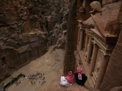 Two Bedouin Men Look Down Upon Tourists Admiring the Facade of Al Khazneh (The Treasury)