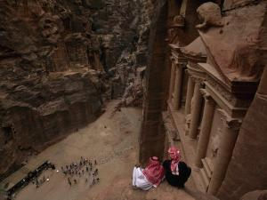 Two Bedouin Men Look Down Upon Tourists Admiring the Facade of Al Khazneh (The Treasury) by Annie Griffiths Belt