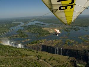 Ultralight Plane Flies Low over Victoria Falls by Annie Griffiths Belt