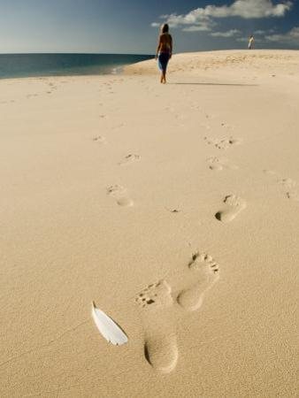 Woman Walks on a Beach Leaving Footprints in the Sand