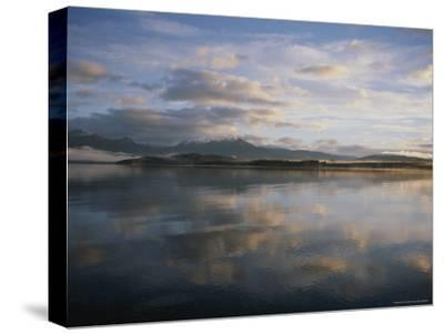 Clouds and Shoreline Reflected in Tranquil Waters at Sunset