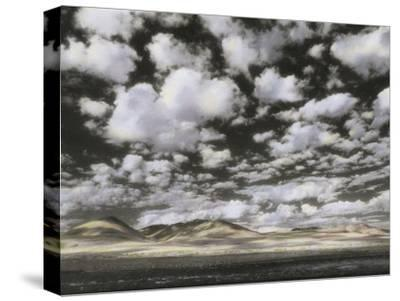 Puffy Clouds Fill a Sky Above Gentle Rolling Hills in the Distance
