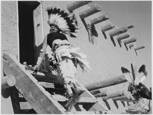 Dance San Ildefonso Pueblo New Mexico 1942 Two Indians In Headdress Ascending Stairs To House 1942 by Ansel Adams