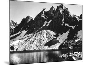 """Kearsarge Pinnacles,"" Partially Snow-Covered Rocky Formations Along the Edge of the River by Ansel Adams"