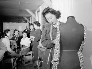 Mrs. Ryie Yoshizawa teaching a dressmaking class to women students at Manzanar, 1943 by Ansel Adams