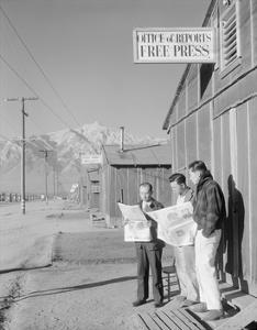 Roy Takeno (Editor) and Group Reading Manzanar Paper [I.E. Los Angeles Times] in Front of Office by Ansel Adams