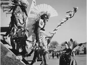 "Three Indians In Headdress Watching Tourists ""Dance San Ildefonso Pueblo New Mexico 1942."" 1942 by Ansel Adams"