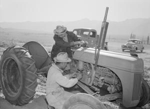 Tractor Repair: Driver Benji Iguchi, Mechanic Henry Hanawa, Manzanar Relocation Center, California by Ansel Adams