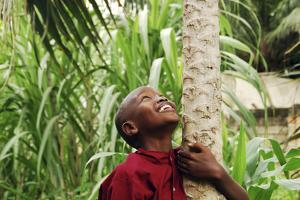 Schoolchild Embracing Tree Trunk and Looking Up, Bujumbura, Burundi by Anthony Asael