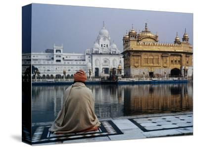 Sikh Man Meditating in Front of the Golden Temple, Amritsar, India
