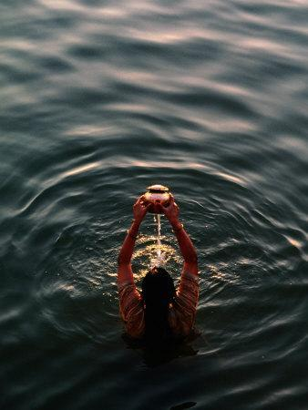 Woman Pouring Water During Morning Puja on Ganges, Varanasi, India