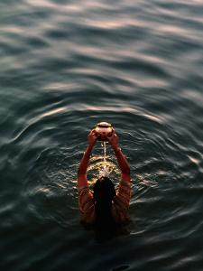 Woman Pouring Water During Morning Puja on Ganges, Varanasi, India by Anthony Plummer