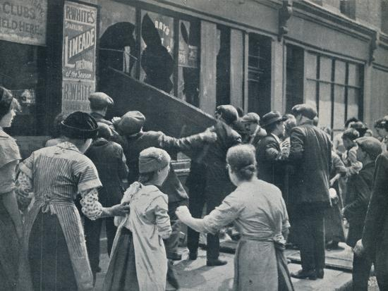 Anti-German rioting in London: A crowd breaking in the windows of a German shop', c1914-Unknown-Photographic Print